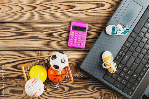 Sports equipment in market basket and calculator beside old