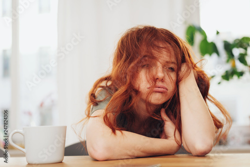 Valokuva  Red-haired girl sitting at table with boring face