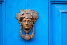 Bronze Door Knocker In The Shape Of A Woman's Head With Elaborate Hair On A Blue House Door