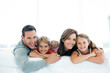 canvas print picture - happy family with two children lying down and looking at camera - portrait