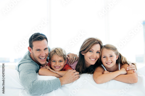 Obraz happy family with two children lying down and looking at camera - portrait - fototapety do salonu