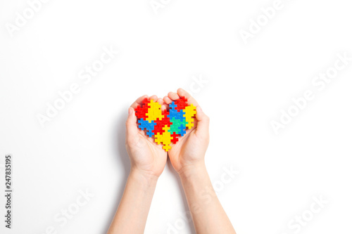 9bde89d0099 Child hands holding colorful heart on white background. World autism ...