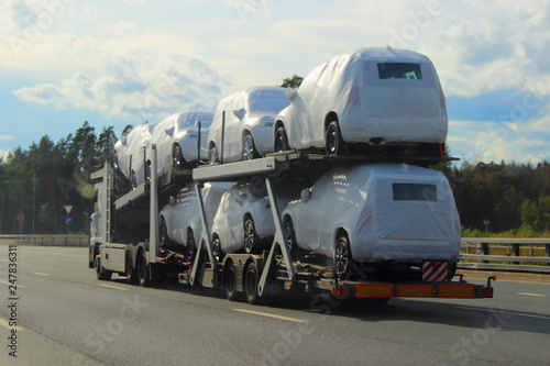 Heavy Car Carrier Truck Transports New Cars In Protective Covers On Semi Trailer Suburban