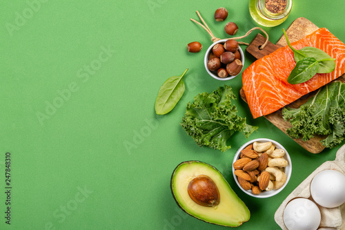 Photo  Keto diet concept - salmon, avocado, eggs, nuts and seeds, bright green backgrou