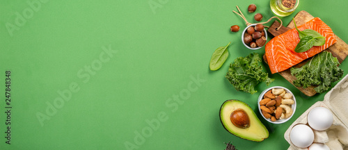 Nourriture Keto diet concept - salmon, avocado, eggs, nuts and seeds, bright green background, top view