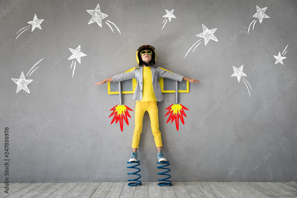 Fototapeta Happy child playing with toy jet pack