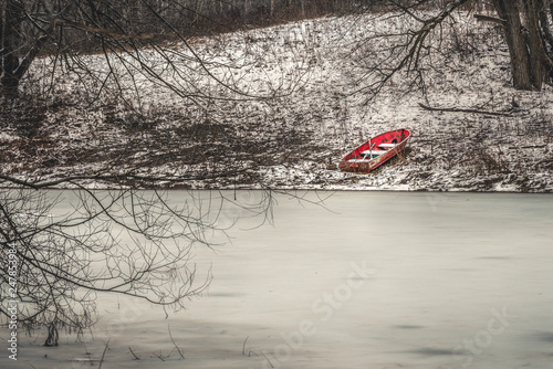 Small abandoned red boat, near frozen edge of lake, aground. Canvas Print