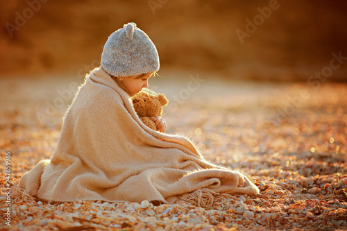 Fototapeta  Side view of little girl in hat cuddling in warm plaid with toy while sitting on