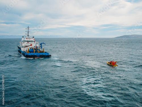 Industrial ship vessel and orange boat in sea Fototapet