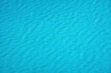 Widok z lotu ptaka na powierzchni wody. Turkusowe morze jako tło. Fale na morzu. Fale jako tło. Obraz wodny