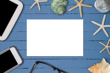 White Paper On Blue Oil Painted Wooden Table With Seashells, Tablet, Smartphone, And A Pair Of Glasses. Copy Space.