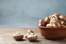 Fresh Champignon Mushrooms And Bowl On Wooden Table, Space For Text