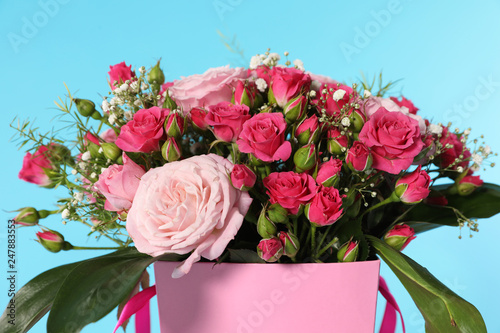 Beautiful bouquet of flowers in paper gift box on color background