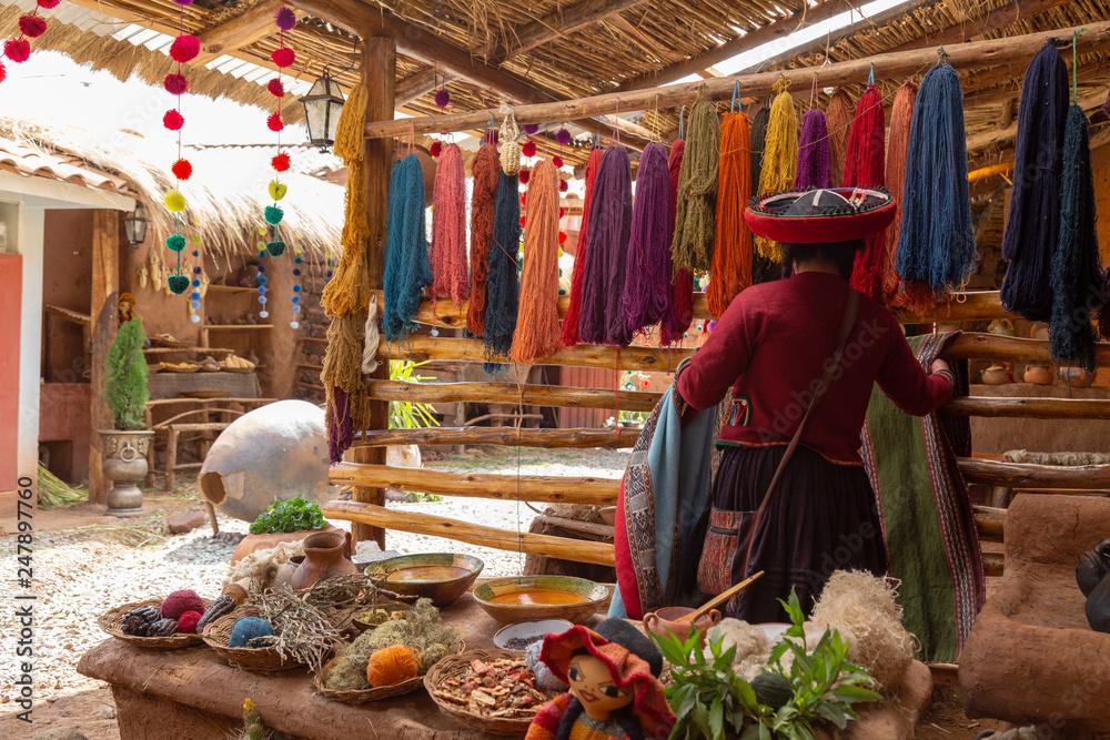 Fototapeta Chinchero, Cusco, Peru. December 2018, Process of natural dyeing of alpaca and llama wool, Quechua woman.