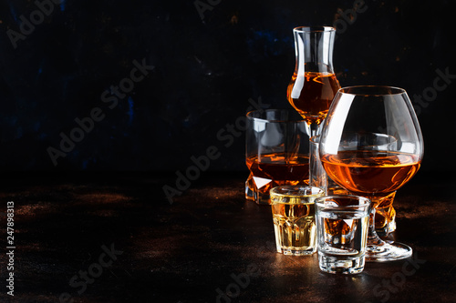 Keuken foto achterwand Bar Selection of hard alcoholic drinks in big glasses and small shot glass in assortent: vodka, rum, cognac, tequila, brandy and whiskey. Dark vintage background, selective focus, copy space
