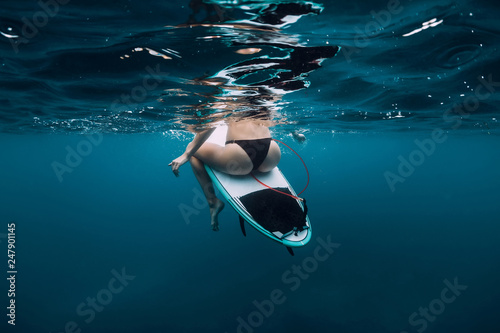 Surfer girl sit at surfboard underwater in blue ocean