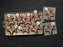 Chocolate Skeleton Cookies On A Tray And Dark Wood Background