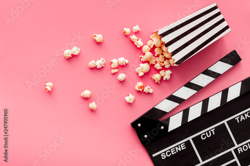 Film watching concept. Clapperboard and popcorn on pink background top view copy space - 247905960