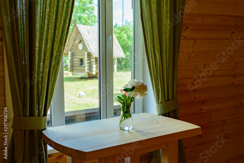 Cuadros en Lienzo a vase with a flower peony stands on a table by the window with a ram in the hut
