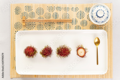 Fényképezés  Top view of a elegant  rambutan desert with chinaware, golden spoon and chopsticks