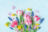 Fototapeta Kwiaty - Bouquet of beautiful spring flowers on pastel blue table top view. Greeting card for International Women Day. Flat lay.