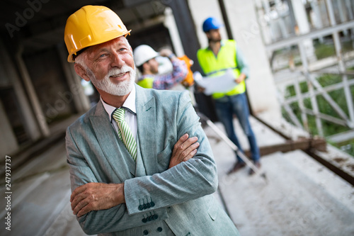 Poster Hoogte schaal Confident construction engineer, architect, businessman in hardhat on building site