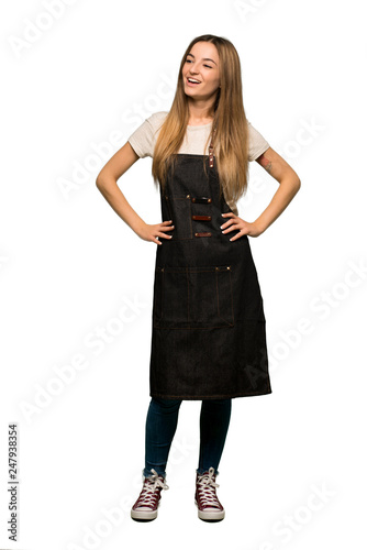 Photo Full body Young woman with apron posing with arms at hip and laughing on isolate