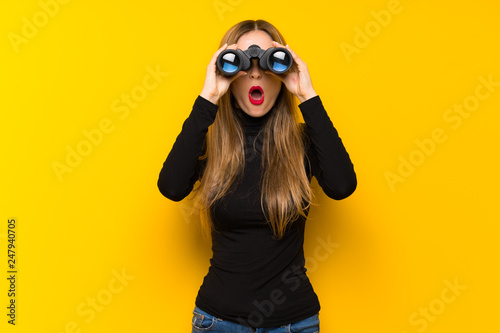 Young pretty woman over yellow background and looking in the distance with binoc Wallpaper Mural