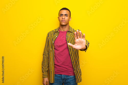 Valokuva  Young afro american man on yellow background making stop gesture denying a situa