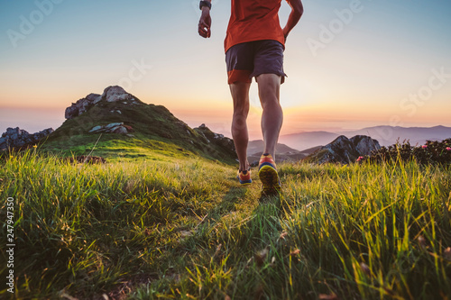 Man trail running on a mountain at the dask Fototapete