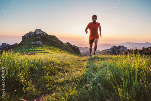 Foto  Man trail running on a mountain at the dask
