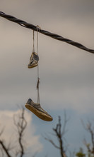A Pair Of Sneakers Hanging Fro...