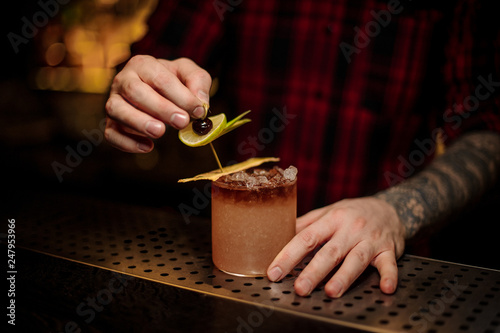 Barman decorating fresh sweet tropic cocktail with fruit