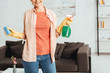 Partial view of woman in yellow rubber gloves holding cleaning spray and sponge