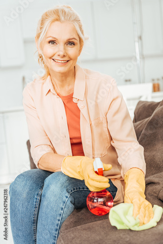 Fotografia  Laughing senior woman in rubber gloves cleaning sofa with spray and rag