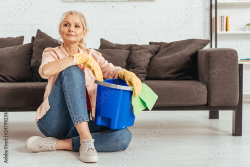 Fotografia  Senior woman sitting on floor with rag and bucket