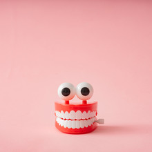 Plastic Toy Teeth Against Pastel Background. Abstract Minimal Composition.