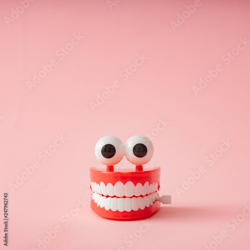 Obraz Plastic toy teeth against pastel background. Abstract minimal composition. - fototapety do salonu