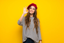 Girl With French Style Over Yellow Wall Showing An Ok Sign With Fingers