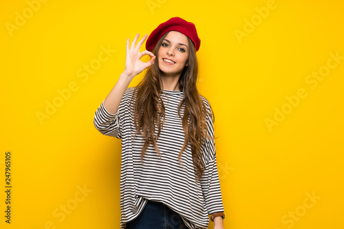 Girl with french style over yellow wall showing an ok sign with fingers Canvas Print