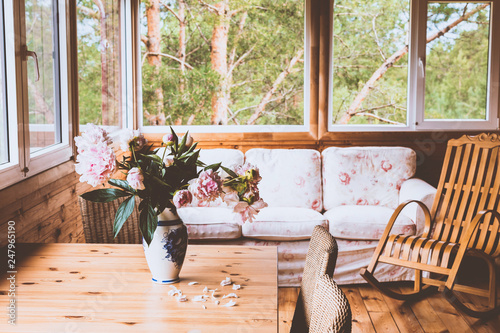 Fotografie, Obraz  A cozy terrace with furniture - a wooden rocking chair, a sofa, peonies in a vase on the table and wicker chairs with a view of the forest