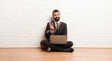 Businessman With His Laptop Sitting On The Floor Happy And Counting Three With Fingers