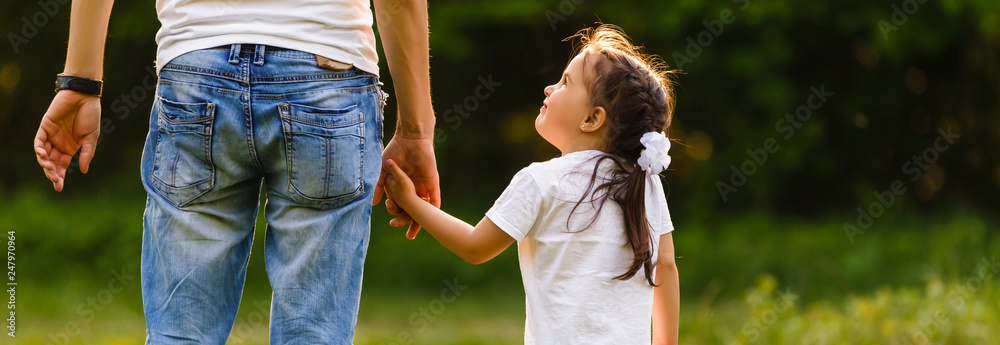 Fototapeta Dad is holding daughter's hand at day time