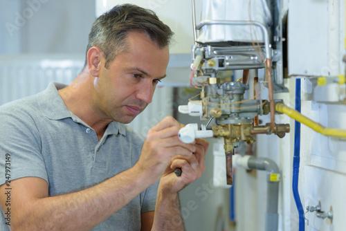 Fotografía  male engineer repairing a gas boiler