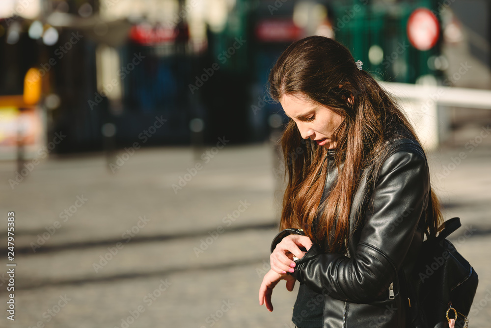 Fototapety, obrazy: Young woman arrives late for an appointment, while waiting in the street.