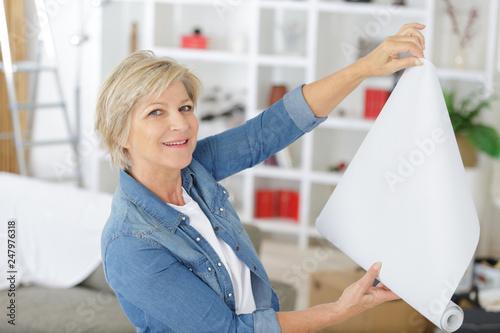 Obraz elderly woman holding paper roller for wallpaper redecoration - fototapety do salonu