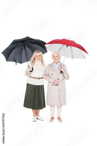 Fotografia  cheerful women standing under umbrellas isolated on white