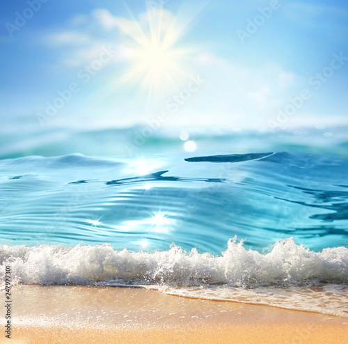 Summer landscape with sea surf, nature of tropical beach with rays of sun light. Golden sand beach, wave sea water, blue sky with white clouds. Copy space, summer vacation concept. Fotomurais