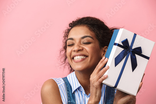 Photo  Emotional excited happy young african woman posing isolated over pink wall background holding present gift box