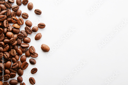 Poster Café en grains Roasted brown coffee beans scattered on white table with a lot copy space for text. Flat lay composition. Close up, top view, background.